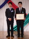 新田社長との記念写真に応じる皆勤のサポートスタッフ
